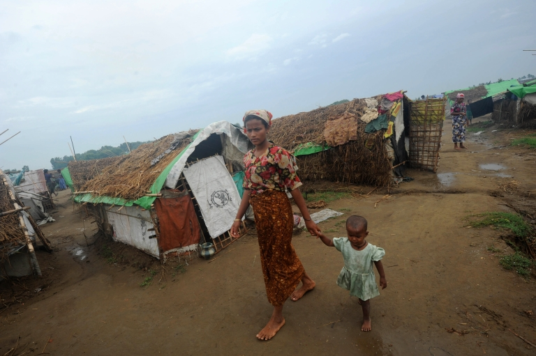 <p>A Rohingya woman and her child walk in front of tents at the Mansi Internally Displaced Persons (IDP) camp on the outskirts of Sittwe on May 15, 2013.</p>