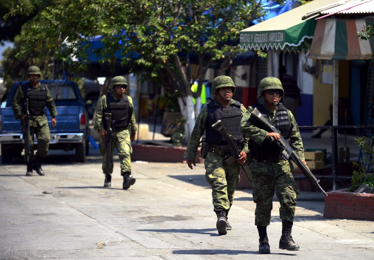 <p>Mexican army soldiers patrol the streets of Buenavista Tomatlan in criminal
