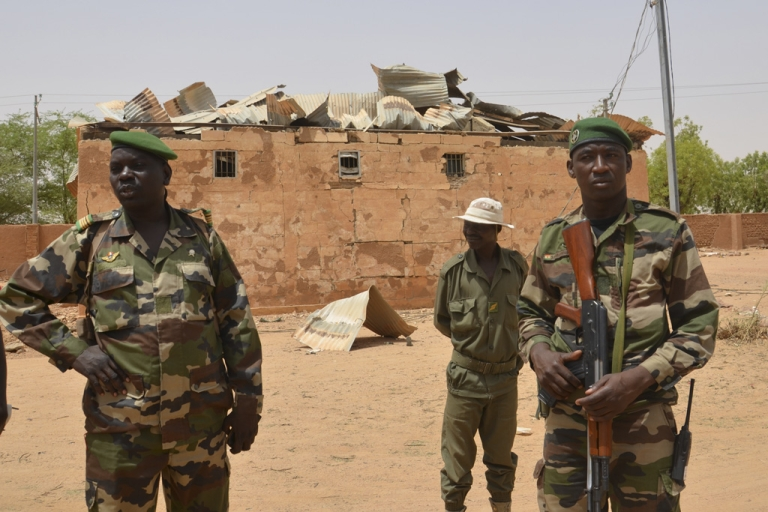 <p>Nigerien soldiers stand near a damaged building at an army base in Agadez on May 26, 2013. Militants linked to Al Qaeda staged twin bombings at the base on May 23. In all, the attack claimed 24 victims and eight militants, according to Niger's Defence Minister.</p>