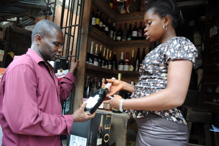 <p>A sales attendant shows a bottle of champagne to a customer at a roadside shop in Lagos, Nigeria on April 23, 2013.</p>