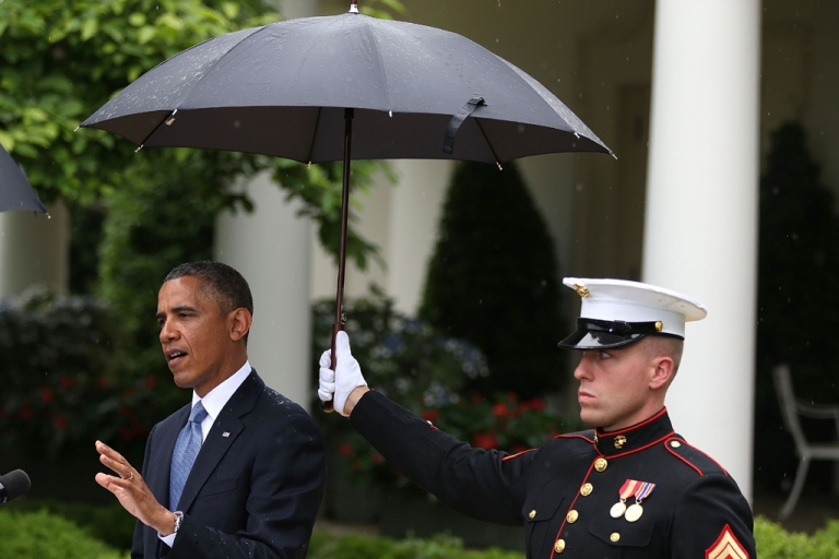 <p>A US Marine holds an umbrella over President Barack Obama as he and Prime Minister Recep Tayyip Erdogan of Turkey (not shown) speak to the media in the Rose Garden at the White House May 16, 2013 in Washington, DC.</p>