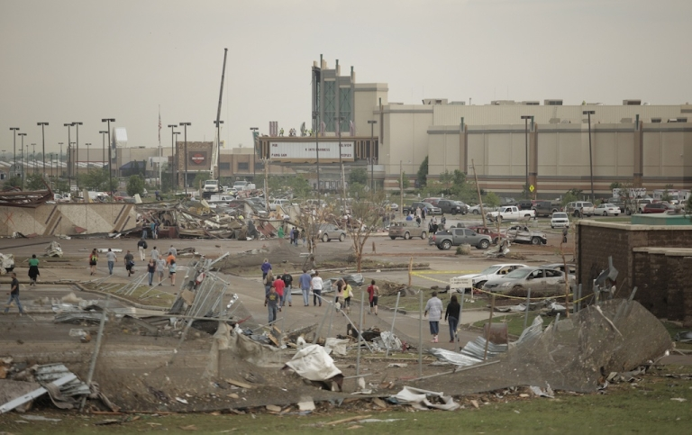 <p>People walk through a damaged area near the Moore Warren Theater after a powerful tornado ripped through the area on May 20, 2013 in Moore, Oklahoma.</p>