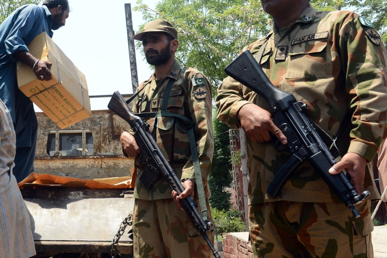 <p>Pakistani soldiers stand guard as government workers load electoral materials onto a truck prior to its transporation for polling stations for the forthcoming parliamentary elections, in Lahore on May 6, 2013.</p>