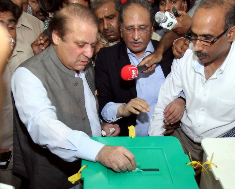 <p>Former Pakistani prime minister Nawaz Sharif (L), casts his vote at a polling station in Lahore on May 11, 2013. Sharif, the frontrunner in Pakistan's landmark election, cast his ballot on May 11 and said he was confident of victory. The vote marks the first time that an elected civilian administration has completed a full term and handed power to another through the ballot box in a country where there have been three military coups and four military rulers.</p>