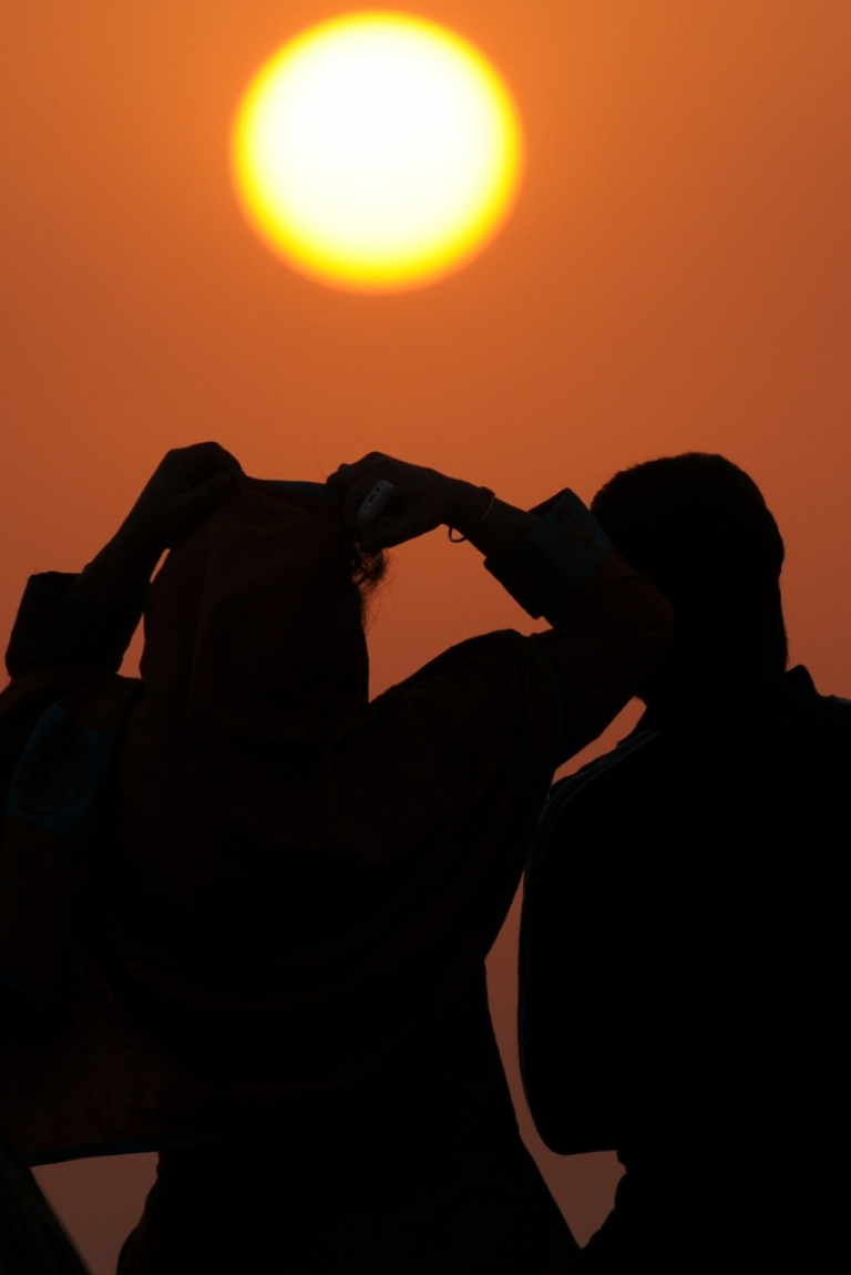 <p>A Pakistani couple looks at the last sunset of the year at Clifton beach in Karachi on December 31, 2011.</p>