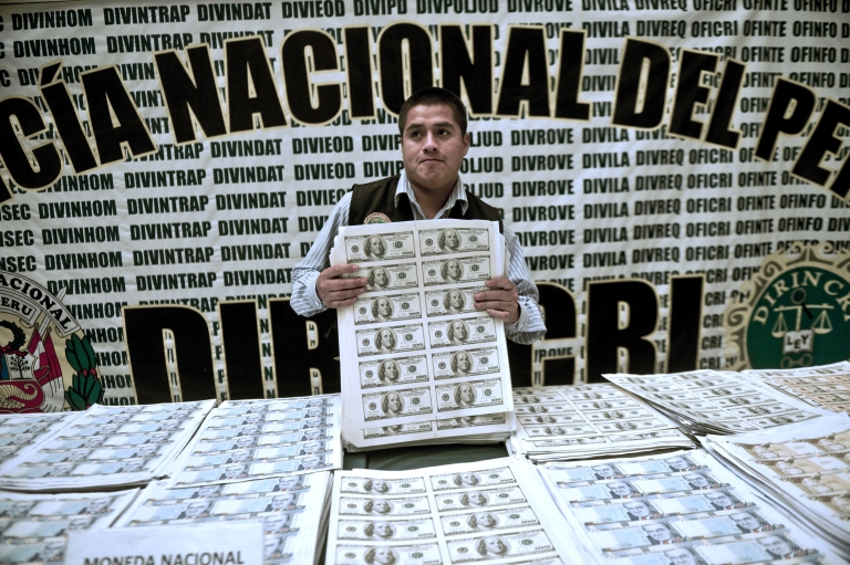 <p>A Peruvian policeman shows printed sheets of counterfeit US $100 bills.</p>