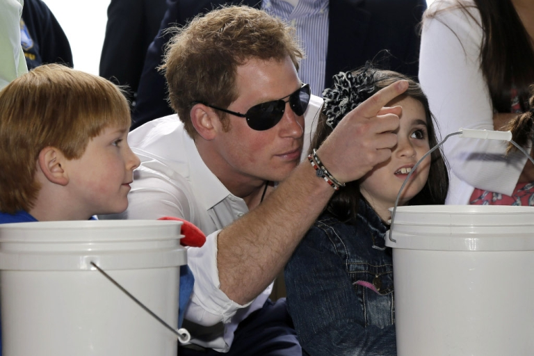 <p>Michael Vanover, 7, looks on as Britain's Prince Harry helps Allie Cirigliano, 7, pick a prize at a Ball Toss game on the boardwalk, while visiting the area hit by Superstorm Sandy May 14, 2013 in Seaside Heights, New Jersey.</p>