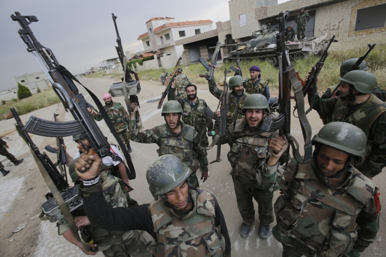 <p>Syrian troops celebrate as they take control of the village of Haydariyah, about seven kilometers outside the rebel-held city of Qusayr, on May 13, 2013.</p>