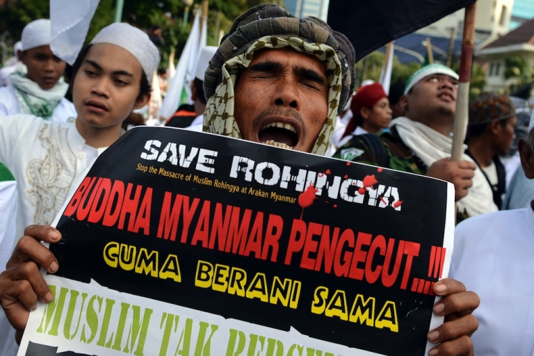 <p>A protester of the Islamic Defenders Front (FPI) holds a placard calling to 'stop the massacre of Muslim Rohingya and Myanmar Buddhists cowards' in Jakarta on May 3, 2013.</p>