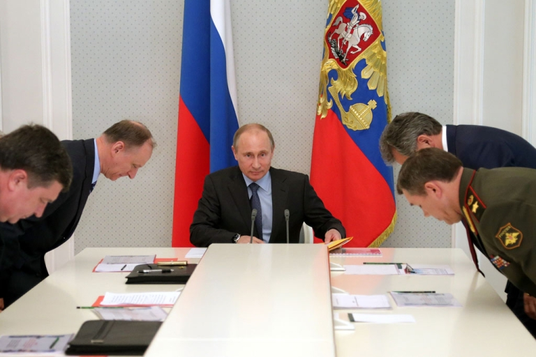 <p>Russia's President Vladimir Putin (C) looks on during his meeting with Defence Ministry top officials and the Security Council members at the Bocharov Ruchei state residence in the Black Sea resort of Sochi, on May 13, 2013. US media reports suggest Russia has sent advanced missiles to Syria as of May 17, 2013.</p>