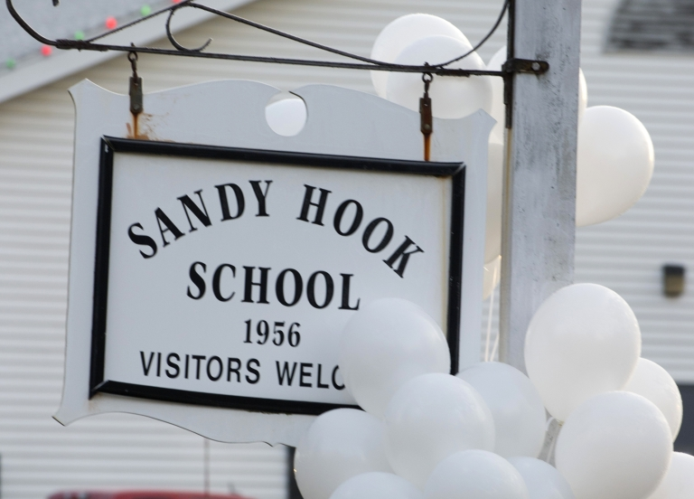 <p>Balloons hang on a sign at the entrance to Sandy Hook School on December 15, 2012 in Newtown, Connecticut. The residents of an idyllic Connecticut town were reeling in horror from the massacre of 20 small children and six adults in one of the worst school shootings in US history. T</p>