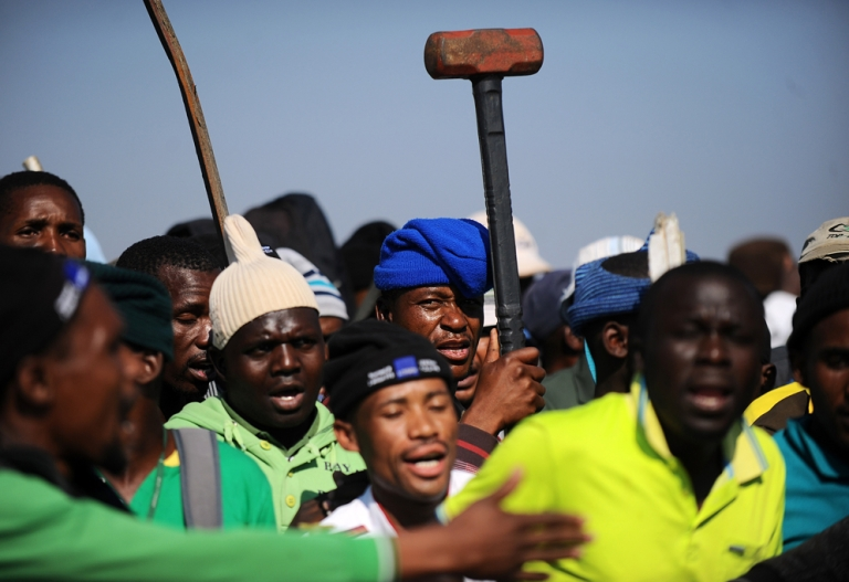 <p>Striking Lonmin mine workers dance and sing as they gather May 15 at the Wonderkop stadium in Marikana during a strike.</p>