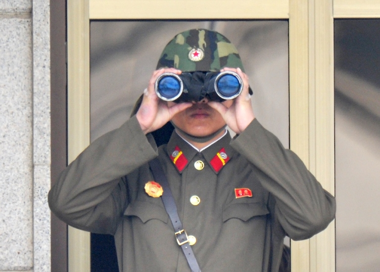 <p>A North Korean soldier watches from his quarters at the truce village of Panmunjom in the demilitarised zone on April 23, 2013.</p>