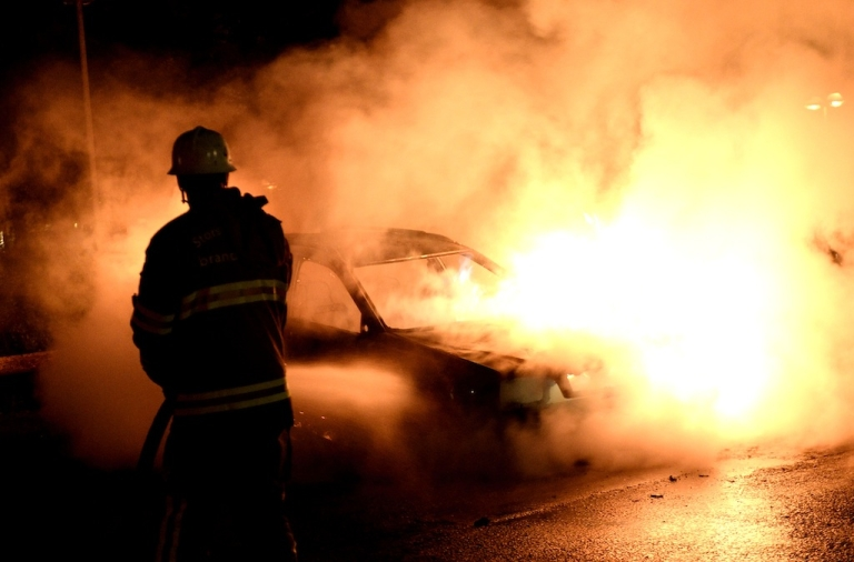 <p>Firemen extinguish a burning car rioters set on fire in Kista, Stockholm on May 21, 2013.</p>