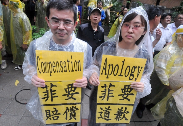 <p>Two people hold protest signs at the Philippine de facto embassy in Taipei during a demonstration on May 13, 2013 against the shooting to death of a local fisherman by Philippine coastguards. The incident has led to escalation of tensions between Taipei and Manila as the Taiwanese sent a fleet of four naval and coastguard frigates to the water area near the Philippines where the 65-year-old fisherman was killed on May 9.</p>