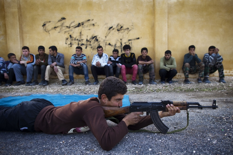 <p>Syrian youth Sobhi, 15, holds an AK-47 assault rifles as he takes part in a military training on January 23, 21013 at a former school turned into a 'military academy' in Tlaleen in the northern Syria's Aleppo province.</p>