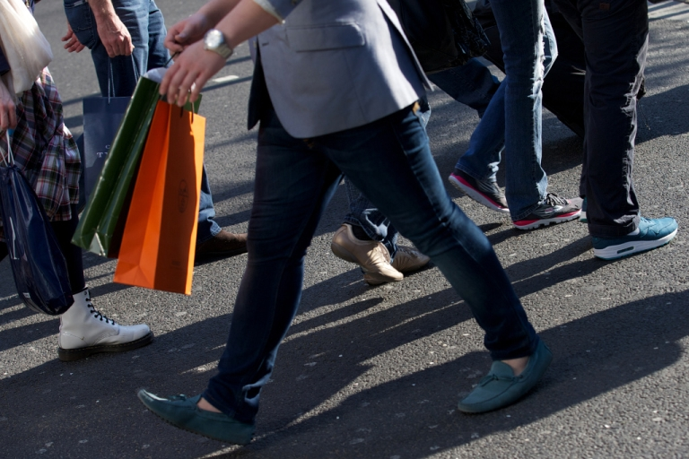 <p>Shoppers carry their purchases as they walk along Oxford Street in central London on April 25, 2013.</p>