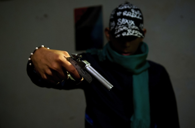 <p>A gang member poses with a homemade gun at the Siloe neighborhood in Cali, Colombia on June 27, 2013. The United Nations has said that Latin America was the least secure region in the world due to crime.</p>