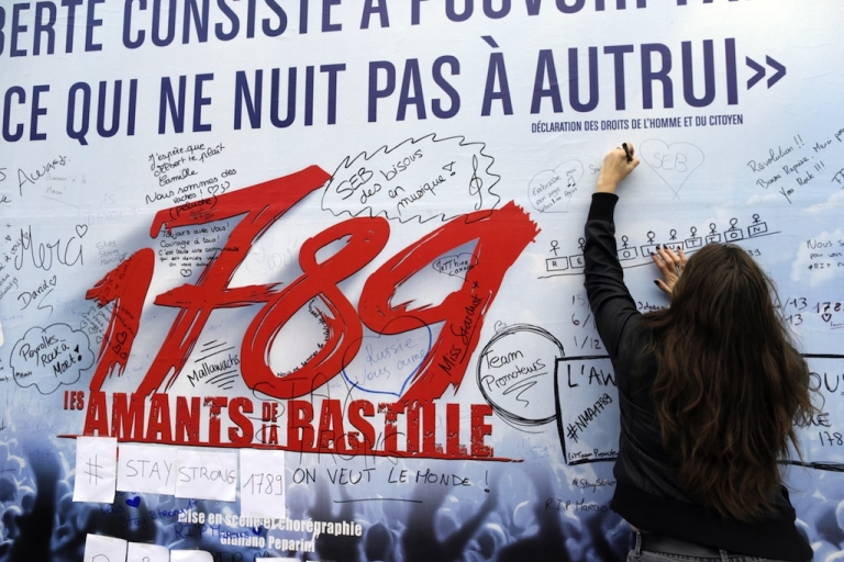 <p>A woman writes down a message on the poster of the musical '1789, The Lovers of Bastille', on November 9, 2013 in Paris, one day after the blast at the Palace of Sports at the Porte de Versailles. One of around 15 people hurt in an accidental explosion during rehearsals for a Paris musical died overnight of a heart attack, police said today</p>