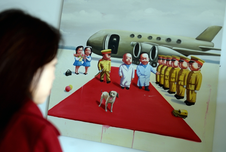 <p>A woman looks at a painting showing officials at an arrival ceremony in Beijing on November 11, 2013. The Chinese Communist Party Central Committee's Third Plenum is currently underway and is expected to focus on economic reforms a year after a closely watched leadership transition. The four-day session of the full 376-member Communist Party Central Committee takes place at a closely guarded hotel and traditionally sets the economic tone for a new government.</p>