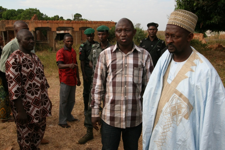 <p>Umar Farouk Mohammed, of Kaduna's Interfaith Mediation Center, on a site visit to Redo, a community plagued with violence between Muslims and Christians. He stands with the head of a Muslim family whose home, in the background, was set ablaze in the communal violence.</p>
