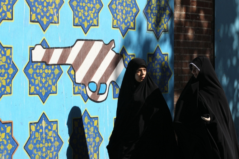 <p>Iranian women walk past a mural of a revolver bearing the colours of the US national flag on the wall of the former US embassy in Tehran on November 2, 2012, during a rally to mark the 33rd anniversary of seizure of the US embassy which saw Islamist students hold 52 diplomats hostage for 444 days.</p>