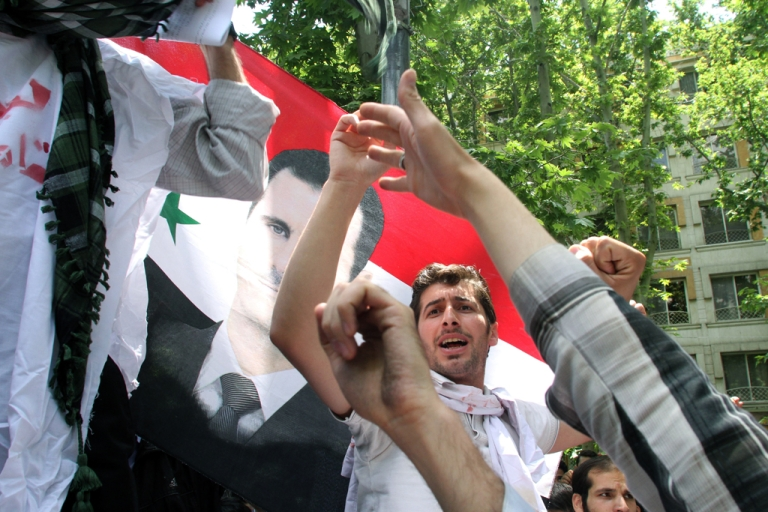 <p>Holding up the Syrian flag, Iranian and Syrian students attend an anti-Israeli demonstration in front of the United Nations offices in Tehran, on May 6, 2013, to condemn Israeli air strikes on targets near the Syrian capital Damascus.</p>