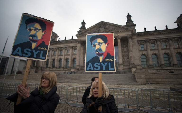 <p>Protesters hold up pictures of US whistleblower Edward Snowden in front of the Reichstag building housing the Bundestag (lower house of parliament) in Berlin on November 18, 2013.</p>