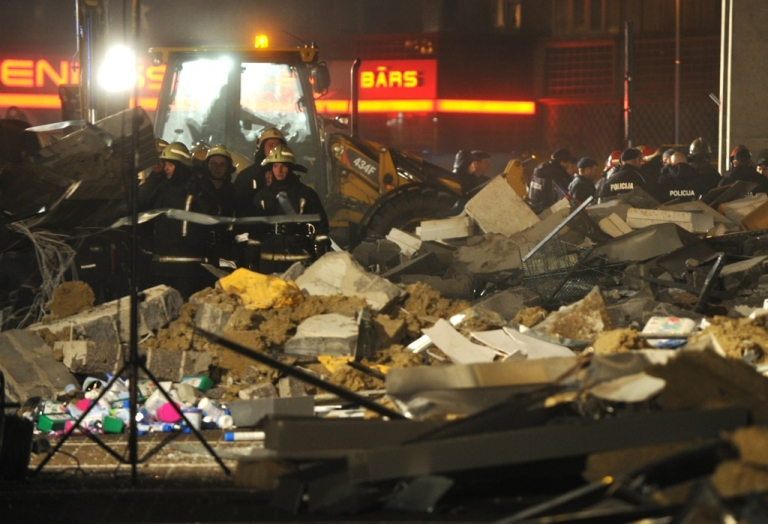 <p>Rescuers search for survivors at the Maxima supermarket in Riga, after the building's roof collapsed on shoppers on November 21, 2013.</p>