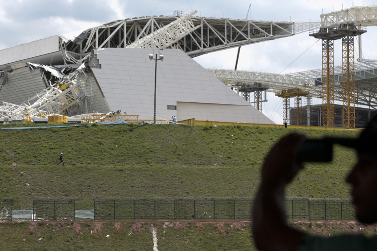 <p>A man takes snapshots of damages at the Arena de Sao Paulo -- Itaquerao do Corinthians -- after a crane fell on Nov. 27, 2013 in Brazil. Two people died and another was injured following the accident on the stadium that will host the opening match of Brazil 2014 FIFA World Cup.</p>