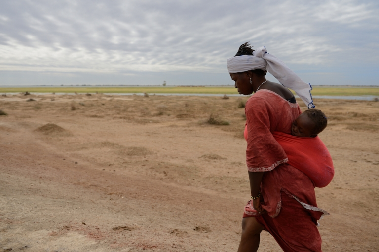 <p>A woman carries her baby in Niafounke, Mali. Climate change is further destabilizing large parts of the Sahel.</p>