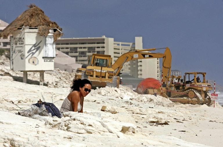 <p>A tourist sunbathes in Cancun in 2006, after Hurricane Wilma devastated the beach. The resort's famous beaches only exist because of multimillion dollar projects to replenish the sand.</p>