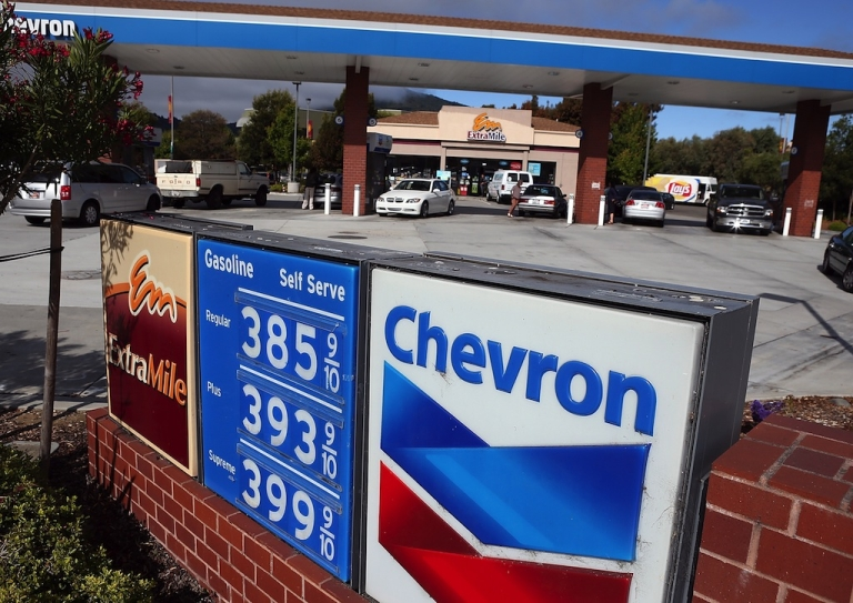 <p>Customers fill up their cars at a Chevron gas station on July 27, 2012 in Greenbrae, California.</p>