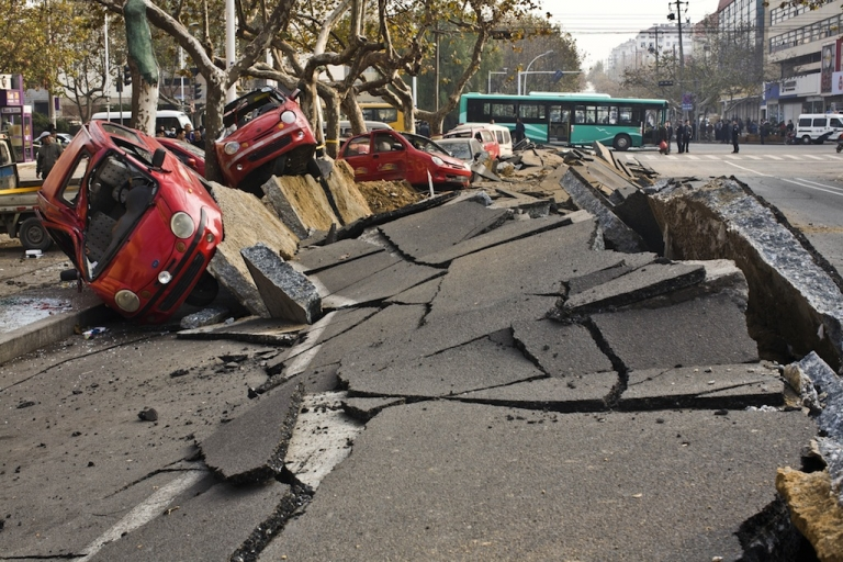 <p>Damaged vehicles lie by a street after an oil pipeline exploded, ripping roads apart, turning cars over and sending thick black smoke billowing over the city of Qingdao, east China's Shandong province on November 22, 2013, killing 35 people, authorities said.</p>