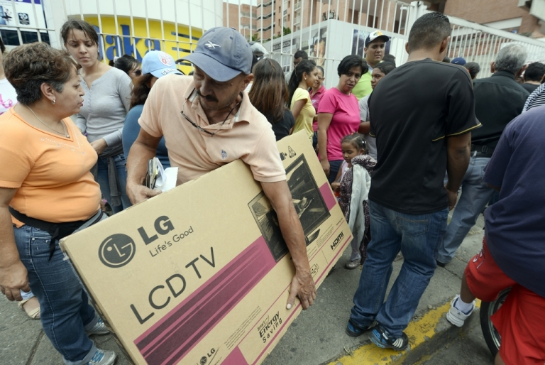 <p>Shoppers loaded with purchases leave a Daka store in Caracas on Nov. 9, 2013. Venezuelan President Nicolas Maduro on Friday ordered the