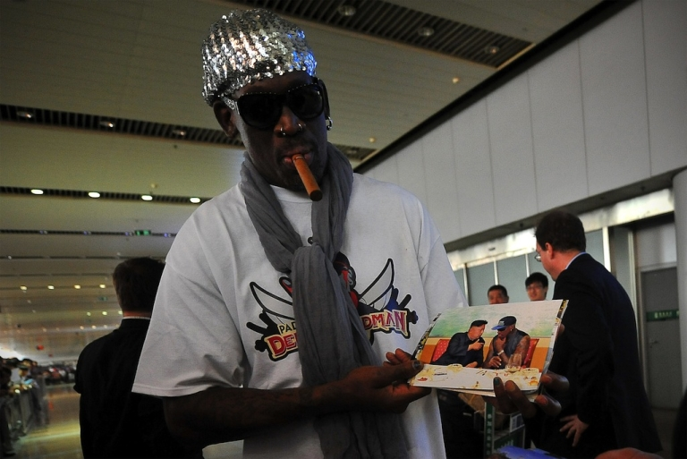 <p>Former US basketball player Dennis Rodman shows pictures of him reportedly with North Korean leader Kim Jong-Un as he arrives at Beijing International Airport on September 7, 2013.</p>