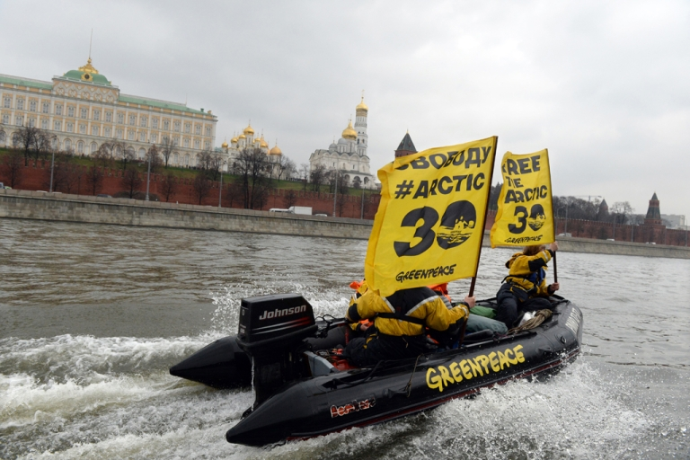 <p>Greenpeace activists hold flags reading