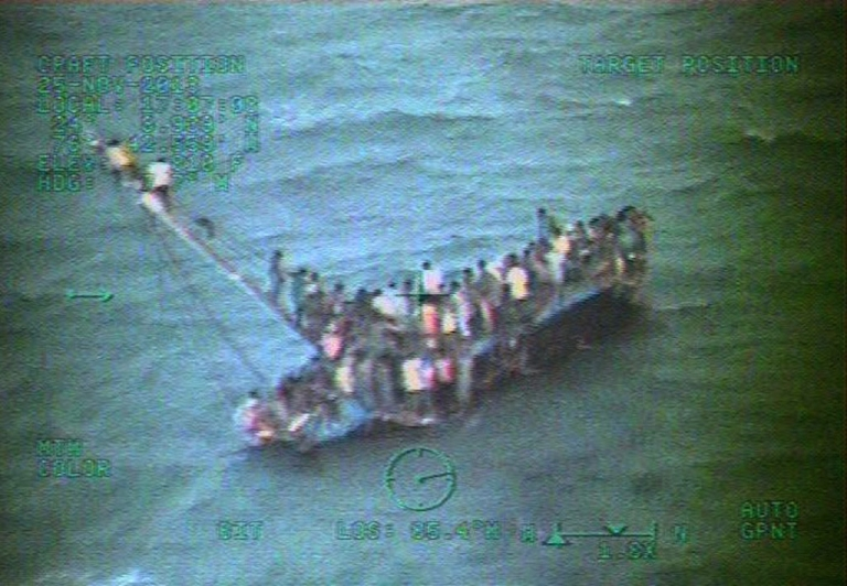 <p>This handout image provided by the US Coast Guard shows about 100 Haitian migrants sitting on the hull of their sailboat on Tuesday, a day after it ran aground and capsized near Staniel Cay in the central Bahamas.</p>