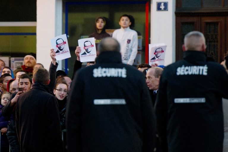 <p>People hold placards representing French President Francois Hollande and reading