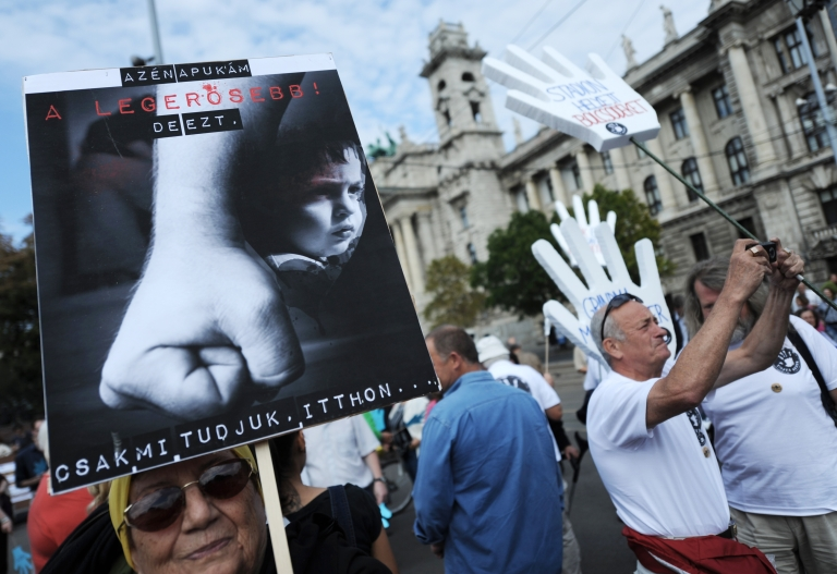 <p>An elderly woman holds a banner that reads 'My father is the strongest man ... but only we know, and only at home' during a demonstration against domestic violence in front of the Hungarian parliament building in Budapest on Sept. 16, 2012.</p>
