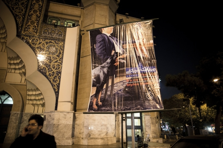 <p>An anti-American poster depicts a US negotiator, sitting at a table with a dog at his side, next to a mosque in Tehran's Palestine square on Oct. 27, 2013. The Tehran municipality has reportedly since removed such displays from the streets of the capital. The move comes as President Hassan Rouhani, a reputed moderate, has made fresh overtures to the West.</p>