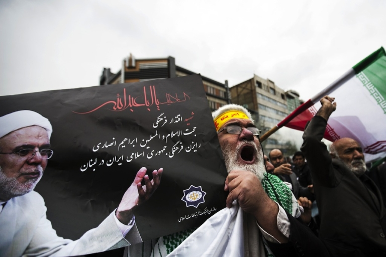<p>An Iranian man holds a picture of Iran's late cultural advisor to Lebanon, Ebrahim Ansari, as he shouts anti-Israeli slogans during his funeral in Tehran on Nov. 22, 2013.</p>