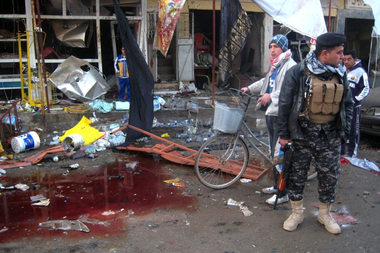 <p>An Iraqi soldier stands near a puddle of blood on the site of bomb attacks on November 24, 2013 in the northern city of Tuz Khurmatu.</p>