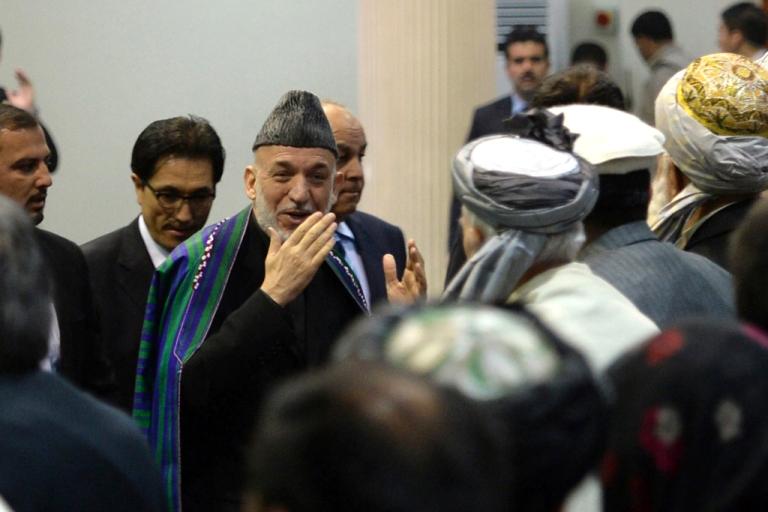 <p>Afghan President Hamid Karzai (C) arrives to address the Afghan Loya Jirga, a meeting of around 2,500 Afghan tribal elders and leaders, on November 21, 2013 in Kabul.</p>