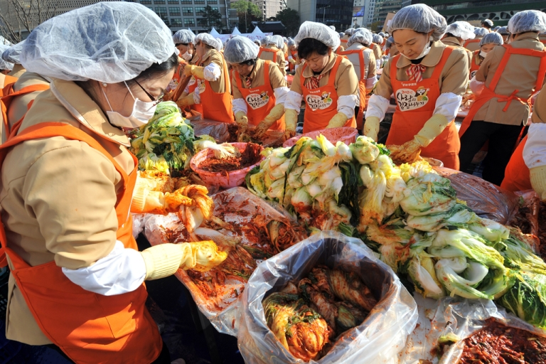 <p>South Korean volunteers make 140 tons of kimchi, a traditional Korean dish of spicy fermented cabbage and radish, in a park outside the metropolitan government building in Seoul on November 15, 2012.</p>