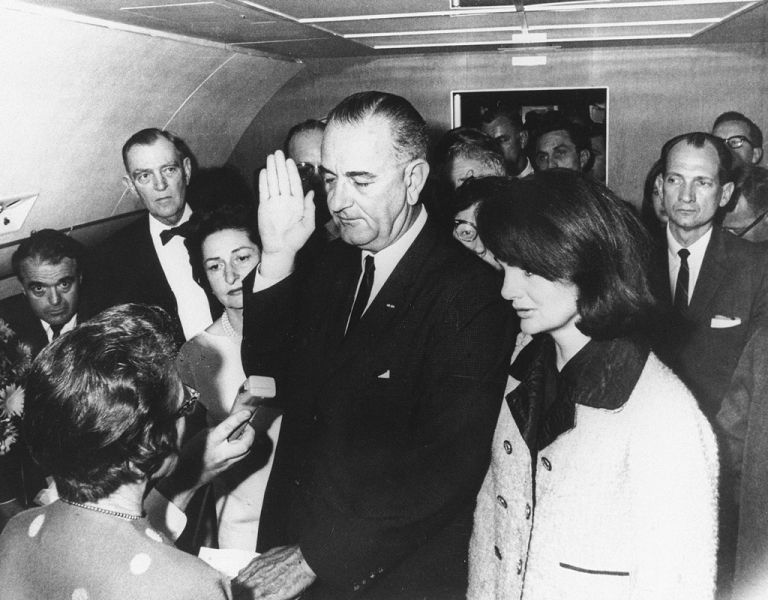 <p>Flanked by Jacqueline Kennedy, right, and his wife Lady Bird Johnson, second left, Lyndon Johnson takes the oath of office of president following the assassination of President John F. Kennedy in Dallas, Nov. 22, 1963.</p>