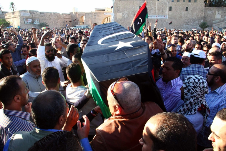<p>Mourners carry the coffin, draped in the Libyan flag, of one of the victims of a shootout the previous day at an anti-militia protest, Martyr's square, Tripoli, Nov. 16, 2013.</p>
