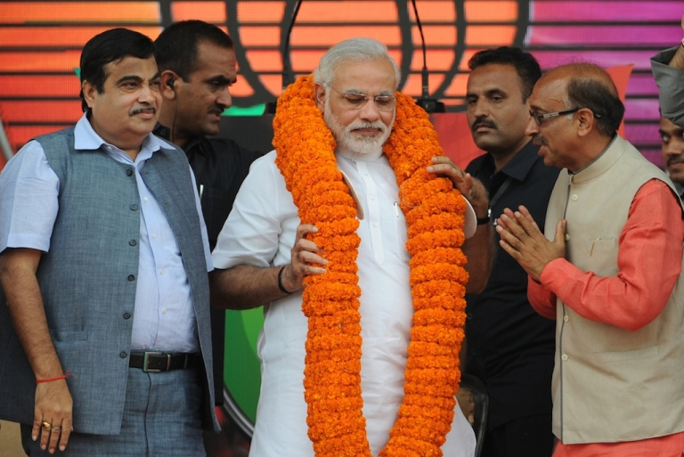<p>Gujarat state Chief Minister and the Bharatiya Janata Party's (BJP) prime ministerial candidate, Narendra Modi (C) wears a garland as he greets supporters during an election rally in New Delhi on September 29, 2013.  Goldman Sachs recently reported that he's viewed favorably by investors. Not everyone agrees.</p>