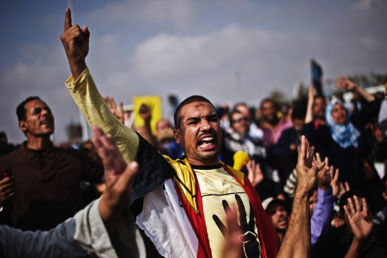 <p>Supporters of ousted president Mohamed Morsi shout slogans outside the Police Academy where his trial is taking place on Nov. 4, 2013, in Cairo.</p>