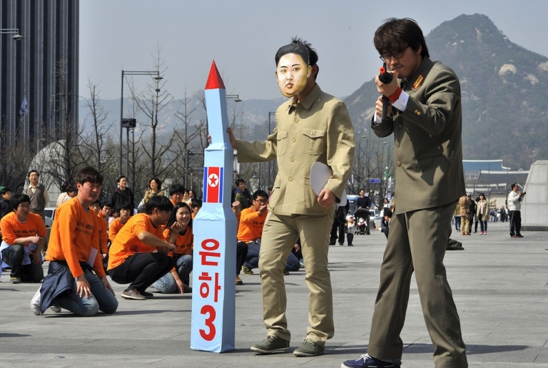 <p>A South Korean activist (C) wearing a mask of North Korean leader Kim Jong-Un holds a mock missile during a rally denouncing North Korea's rocket launch and the three-generational dictatorship, in Seoul on April 15, 2012. Some of the